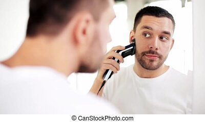 man shaving beard with trimmer at bathroom - beauty,...