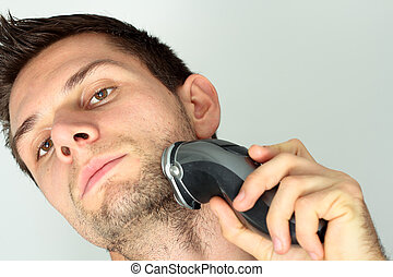 Man shaving face with electric razor