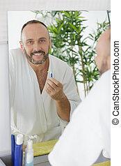 man shaving in a mirror