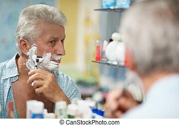 man shaving in bath - Portrait of a senior man shaving in...
