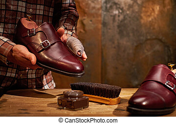 Man shining shoes with a rag.