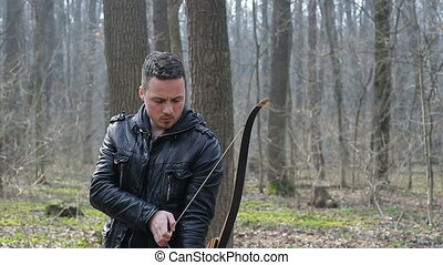 Man shoot with a bow in the forest
