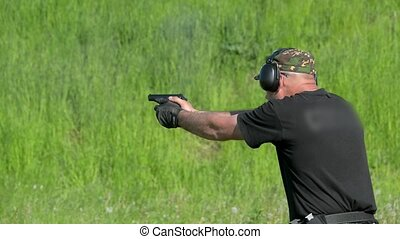 Man shoot with a gun in targets on shooting range.