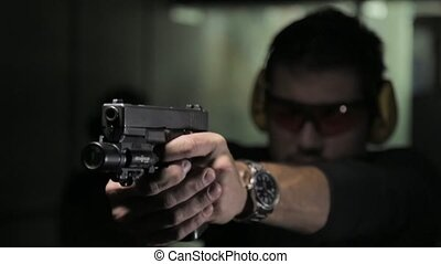 Man shooting a gun - pistol shooting indoor
