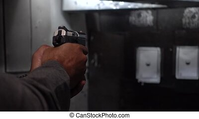 Man shooting a gun in a range - shooting targets with gun