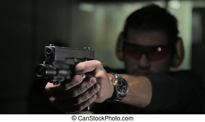 Man shooting a gun with audio - pistol shooting indoor
