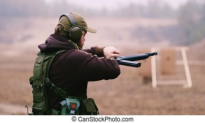 Man shooting a shotgun rear view