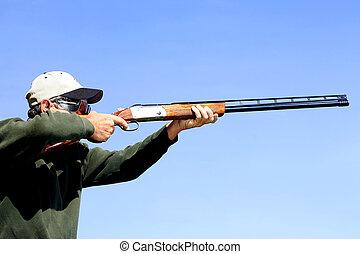 Man Shooting Skeet - Man shooting a shotgun. Bird hunting or...