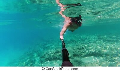 Man shooting underwater video about himself by his action camera