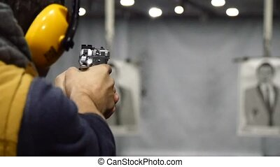 Man shooting with a pistol at the shooting range, focus on...