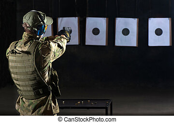 Man shooting with gun at a target in shooting range