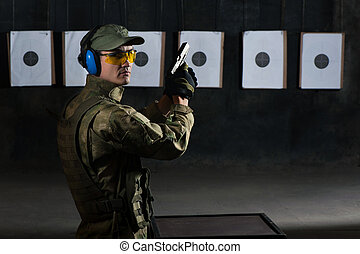 Man shooting with gun at a target in shooting range