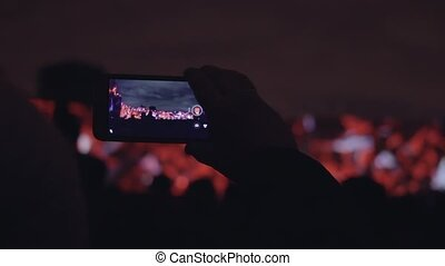 Man shoots 3D mapping light show on a mobile phone. Hands of...