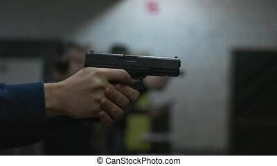 man shoots a gun at shooting range.