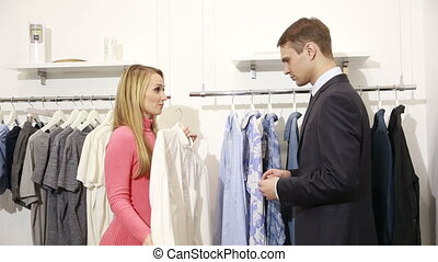 Man shop assistant showing shirt to woman at the mall. man in a business suit looking shirt