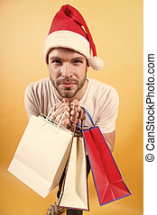 Man shopper in santa hat with paperbags