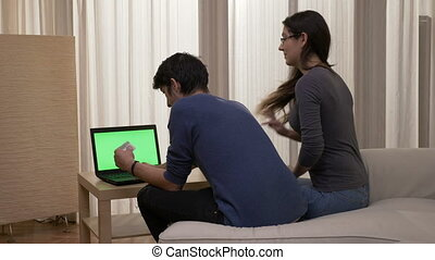 Man shopping online introducing credit card data to buy gifts for his happy girlfriend who kisses and hugs his partner