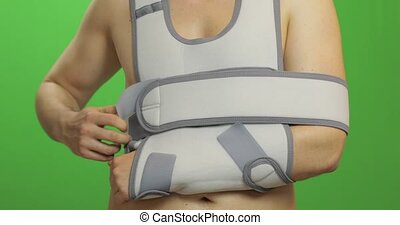 Man with shoulder injury. Patient in a bandage for fixing of an elbow joint and a humeral belt. Dislocations of arm of the forearm, shoulder. Broken bones. Arm brace