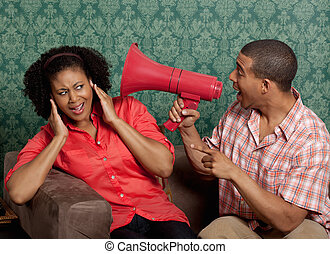 Man shouting through megaphone by woman with hands to ears
