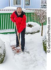 man shoveling snow at - a man shovels snow from a new way....