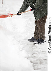 Man shoveling snow from the sidewalk in front of his house
