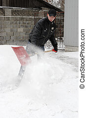 man shoveling snow in a snow storm