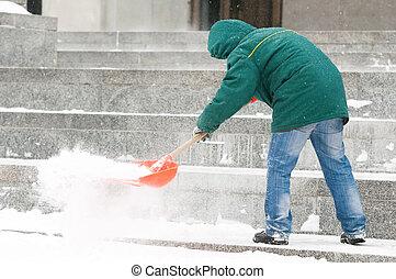 Man shoveling snow - communal services worker in uniform...
