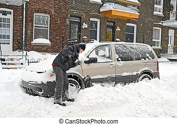 Man shovelling and removing snow from his car during a snow ...