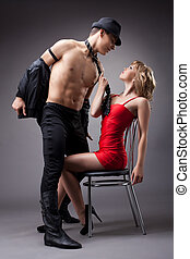 man show striptease for woman in red