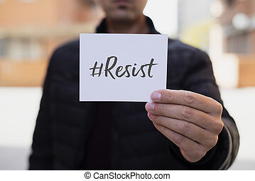 man showing a note with the hashtag resist