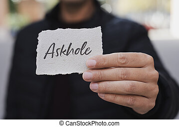 man showing a note with the word askhole in it