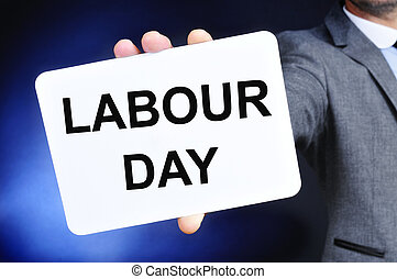 man showing a signboard with the text labour day