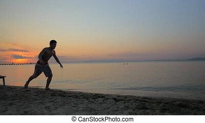 Man showing acrobatics at seaside during sunset - Slow...