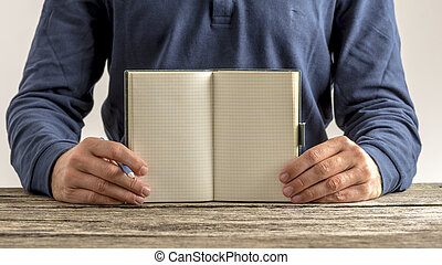 Man showing an open blank note pad with pencil in his hand