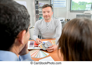 Man showing color swatches to couple