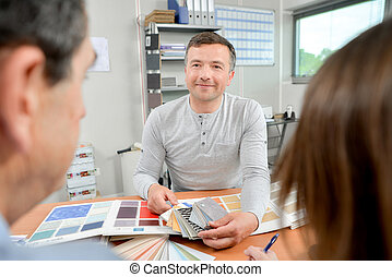 man showing colour charts to couple