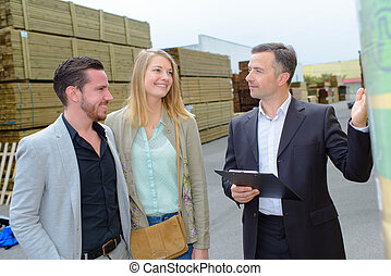 Man showing couple around a builder's yard