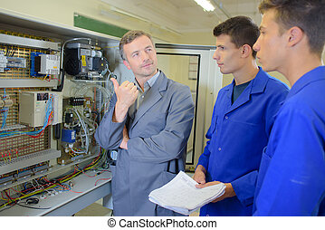 Man showing equipment to two apprentices