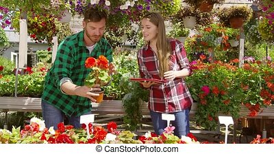 Man showing flower to woman