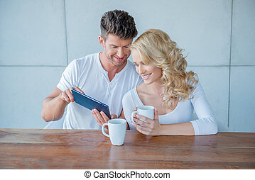 Man showing his wife something on a tablet