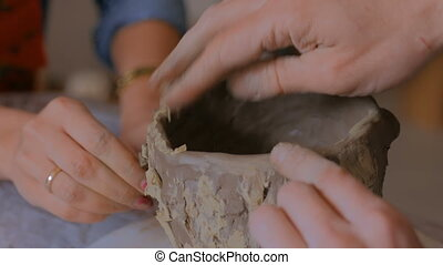 Man showing how to make clay mug in pottery studio