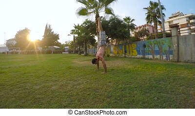 Man showing impressive strength, doing a handstand in a park