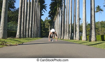 Man showing impressive strength, doing a handstand on path in a rainforest among palm trees