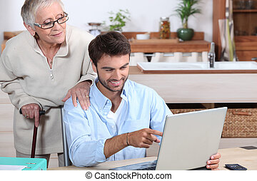Man showing old lady how to use computer