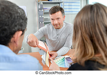 Man showing paint samples to a couple