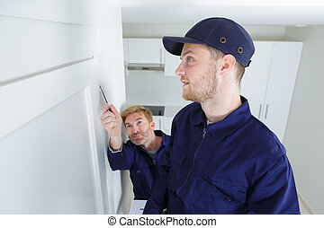 man showing painter man where to paint on the wall