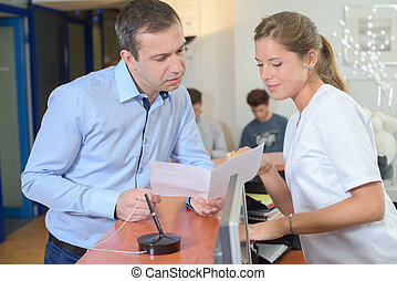 Man showing paperwork to lady at reception