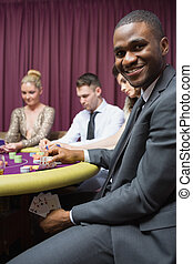 Man showing poker hand under table