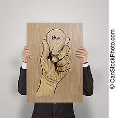 man showing poster of Hand drawn light bulb with IDEA word on wooden board as concept