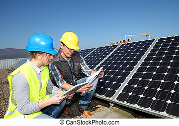 Man showing solar panels technology to student girl